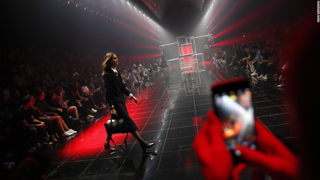 A woman uses her phone to take a photo of a model during a Hugo Boss fashion show in Berlin on Saturday, September 2.
