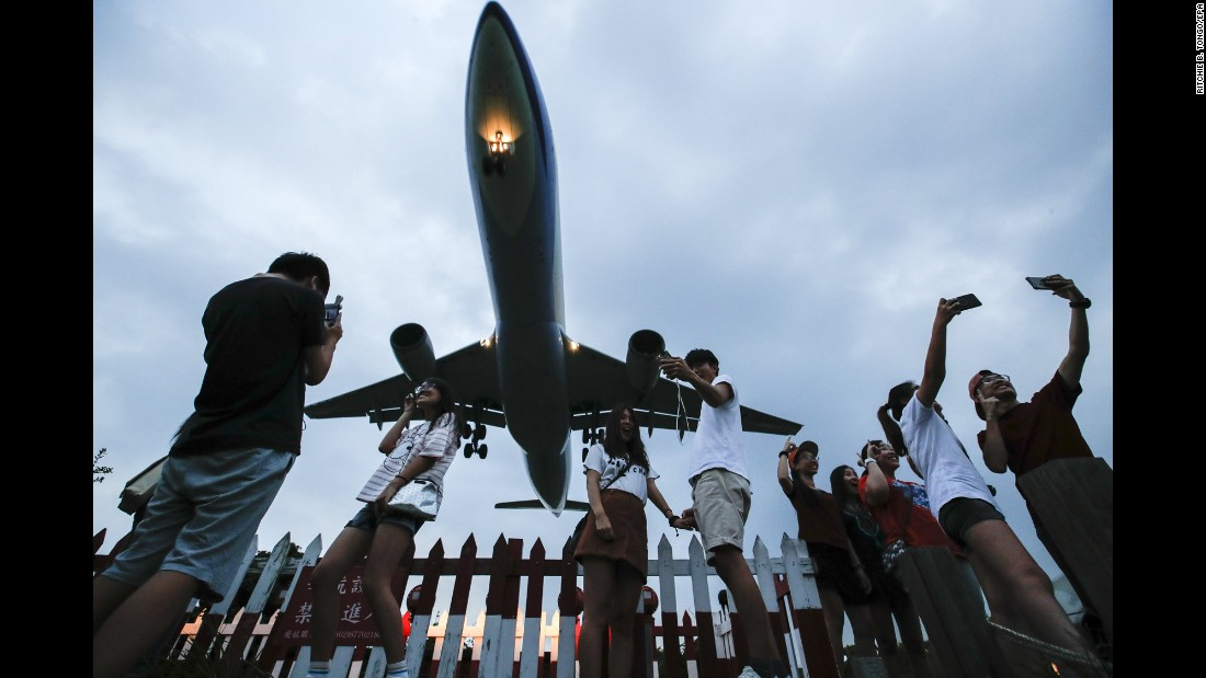 People take photos of an approaching passenger plane in Taipei, Taiwan, on Wednesday, September 6.