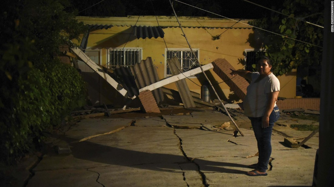 A woman gestures toward her earthquake-damaged home in Coatzacoalcos, Mexico.