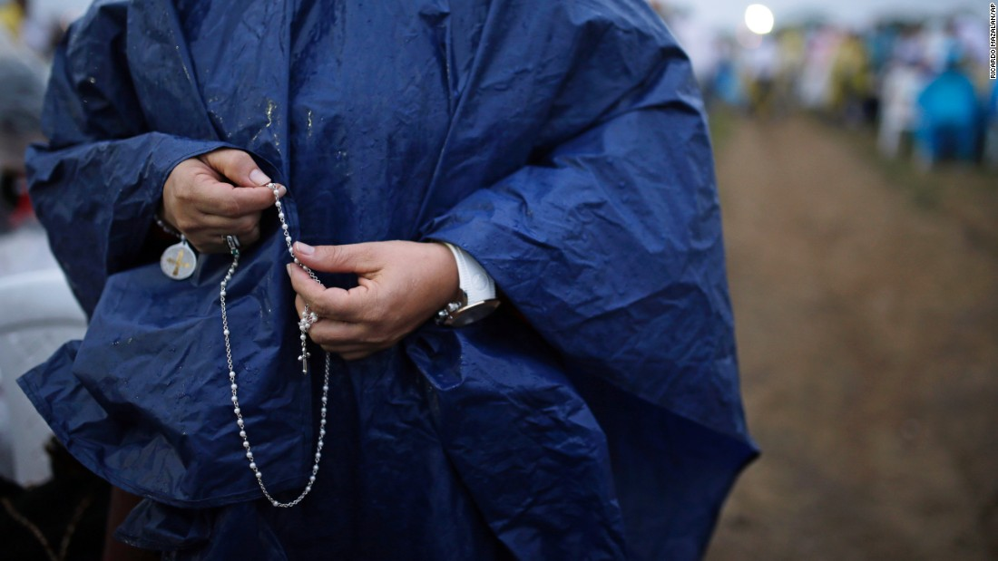 A woman holding a rosary awaits the start of a Mass in Villavicencio on September 8.