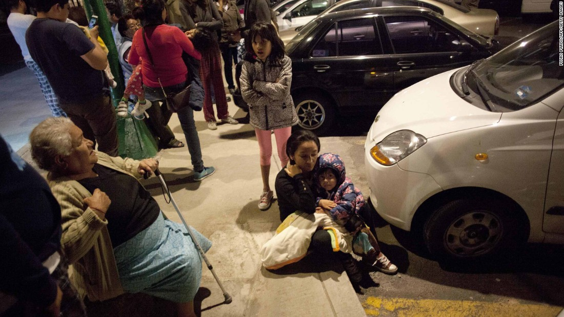 People sit on a sidewalk in Mexico City after the quake.