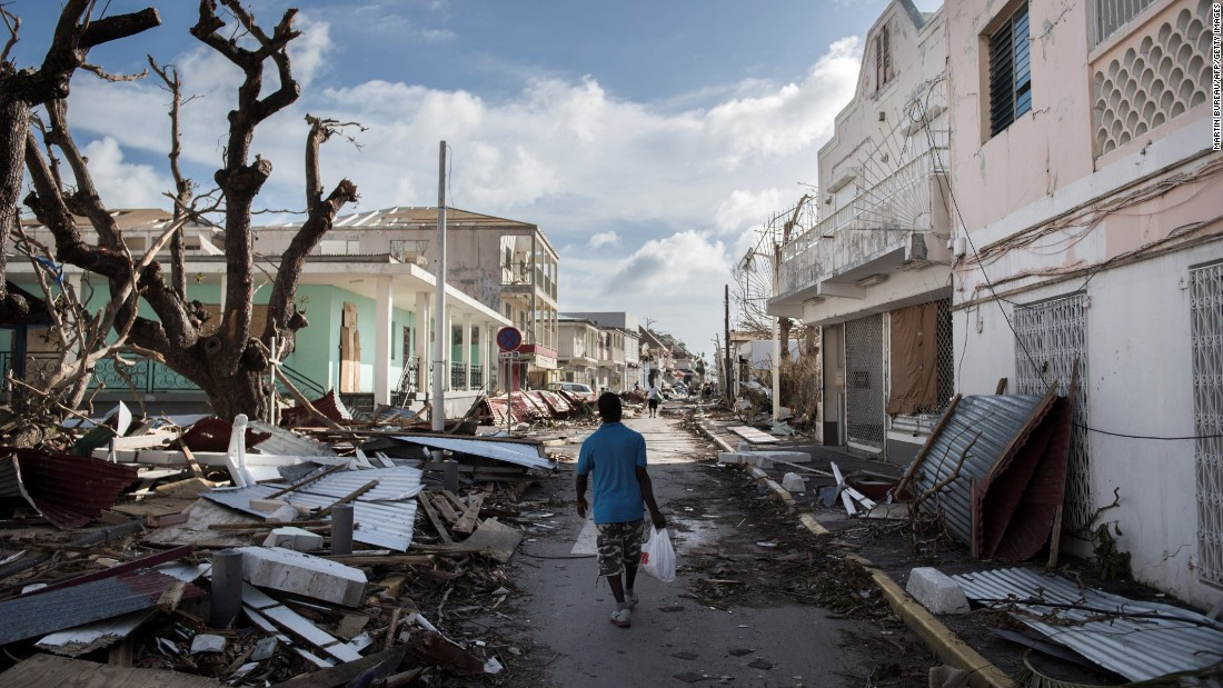 A man walks on a St. Martin street covered in debris on September 8.