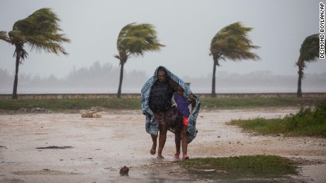 A woman and child use a blanket as protection from wind and rain as they walk Friday in Caibarien, Cuba.