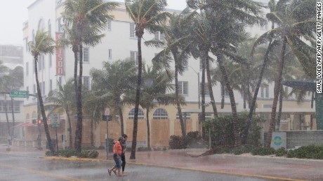 People walk down the street as winds and rain begin to hit as outer bands of Hurricane Irma arrive in Miami Beach, Florida, September 9, 2017. Hurricane Irma weakened slightly to a Category 4 storm early Saturday, according to the US National Hurricane Center, after making landfall hours earlier in Cuba with maximum-strength Category 5 winds. / AFP PHOTO / SAUL LOEB        (Photo credit should read SAUL LOEB/AFP/Getty Images)