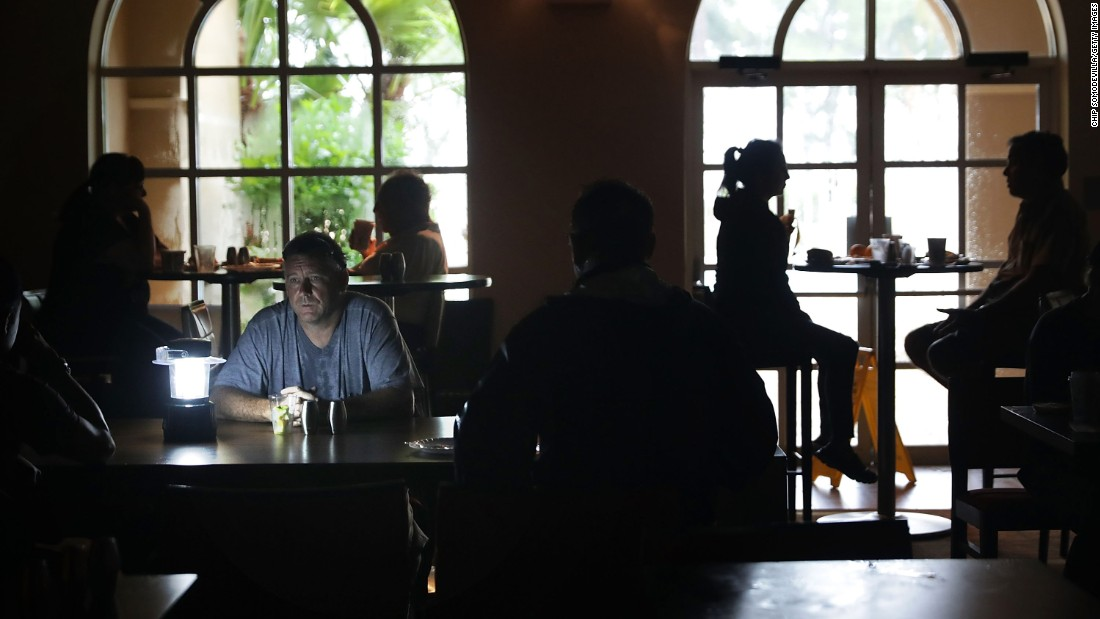 Hotel guests eat breakfast by lamplight after the Courtyard Marriott was left without power in Fort Lauderdale on September 10.