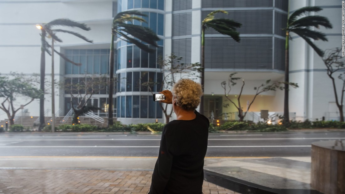 A man records the gusty winds going through downtown Miami on September 10.