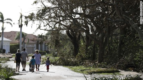 A family walks through a street littered with fallen branches in Marco Island on Monday, a day after Hurricane Irma struck.