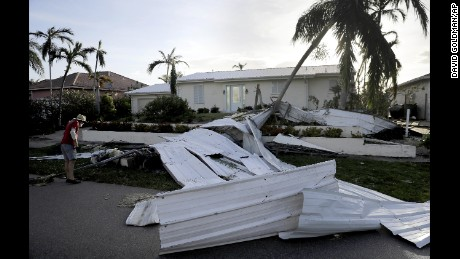 A roof is strewn across a home's lawn as Rick Freedman checks his neighbor's damage.