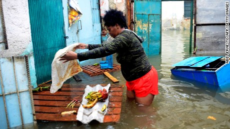 A woman tries to rescue some food from her flooded house in downtown Havana on September 10.