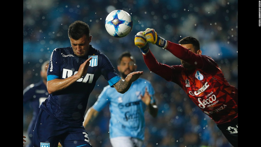 Temperley goalkeeper Josue Ayala tries to punch the ball away from Racing Club forward Enrique Triverio during a league match in Avellaneda, Argentina, on Saturday, September 9.