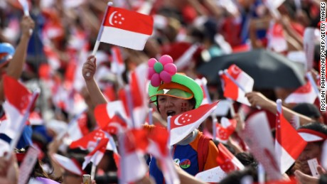 Spectators wave Singaporean national flags during their country's 52nd National Day parade and celebration in Singapore on August 9, 2017.