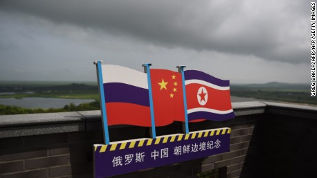This photo taken on June 25, 2015 shows the flags of Russia (L), China (C) and North Korea (R) on a viewing tower on the border between the three countries in Hunchun, China's northeast Jilin province.