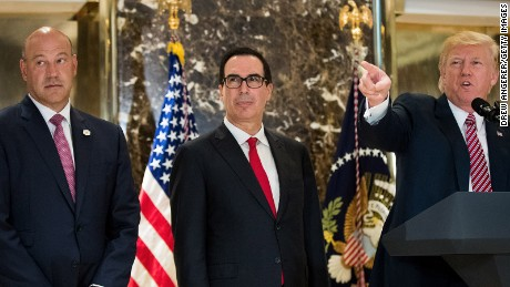 Director of the National Economic Council Gary Cohn and Treasury Secretary Steve Mnuchin look on as US President Donald Trump delivers remarks following a meeting on infrastructure at Trump Tower, August 15, 2017 in New York City.