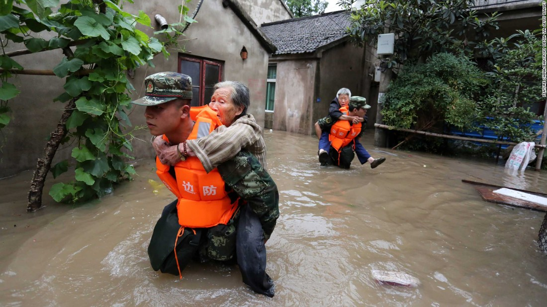 During a period of heavy flooding in Nanjing, paramilitary policemen carried residents from their homes.
