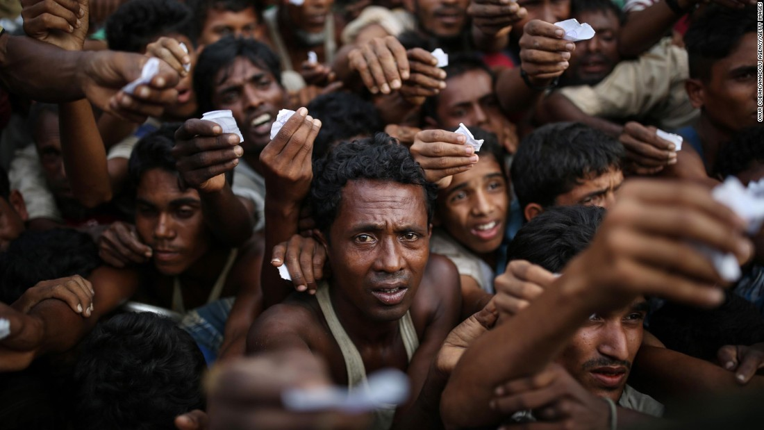 Rohingya men reach out for relief supplies on September 9, at a refugee camp in Bangladesh.