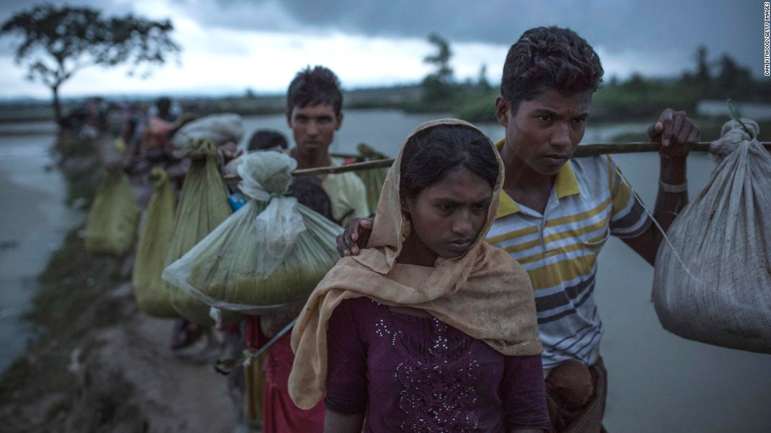 Rohingya refugees walk across paddy fields on September 9, after crossing the border in Gundum, Bangladesh.