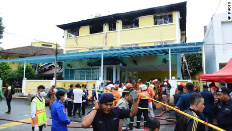 Police and rescue personnel work at an Islamic religious school in Kulala Lumpur that was cordoned off after a fire on September 14.