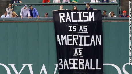 "BOSTON, MA - SEPTEMBER 13: A banner with the message ""Racism is as American as baseball"" is draped over the Green Monster during the fourth inning of the game between the Boston Red Sox and the Oakland Athletics at Fenway Park on September 13, 2017 in Boston, Massachusetts. (Photo by Maddie Meyer/Getty Images)"