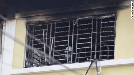 Forensic police officer investigates burnt windows at an Islamic religious school following a fire on the outskirts of Kuala Lumpur Thursday, Sept. 14.