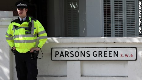 An officer stands next to a street sign near Parsons Green Underground Station on Friday.