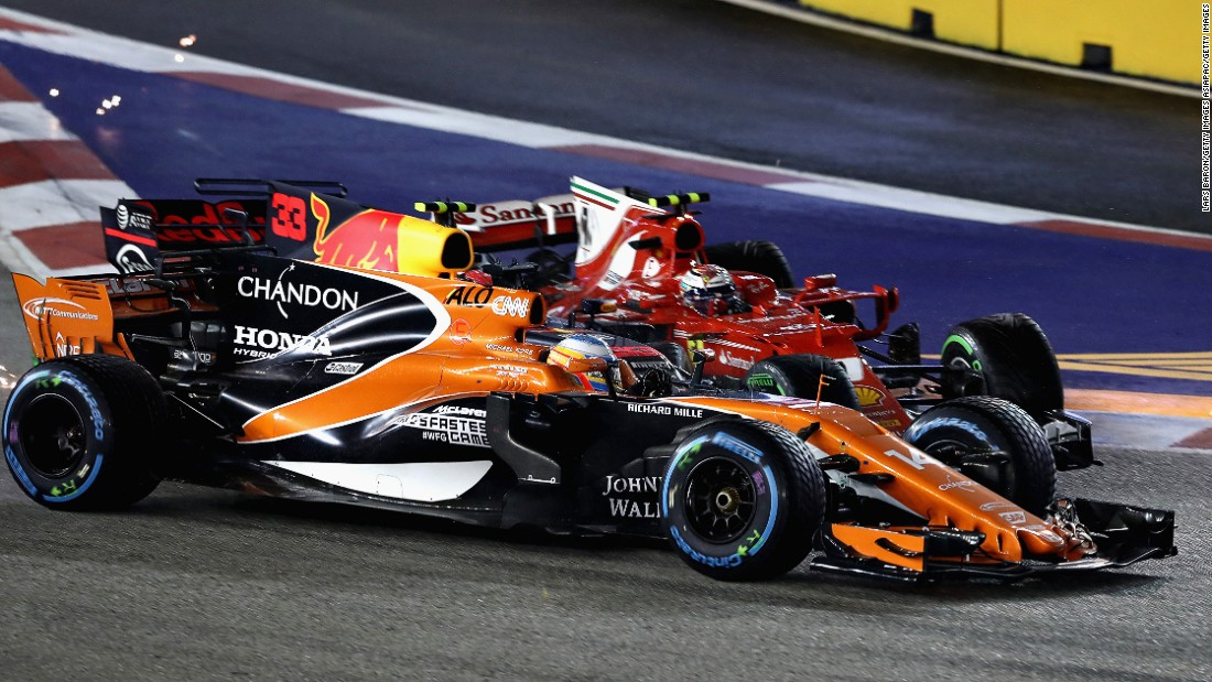 Count the cars... McLaren's Fernando Alonso, Max Verstappen and Kimi Raikkonen collide at the first corner on lap one of the Singapore Grand Prix.