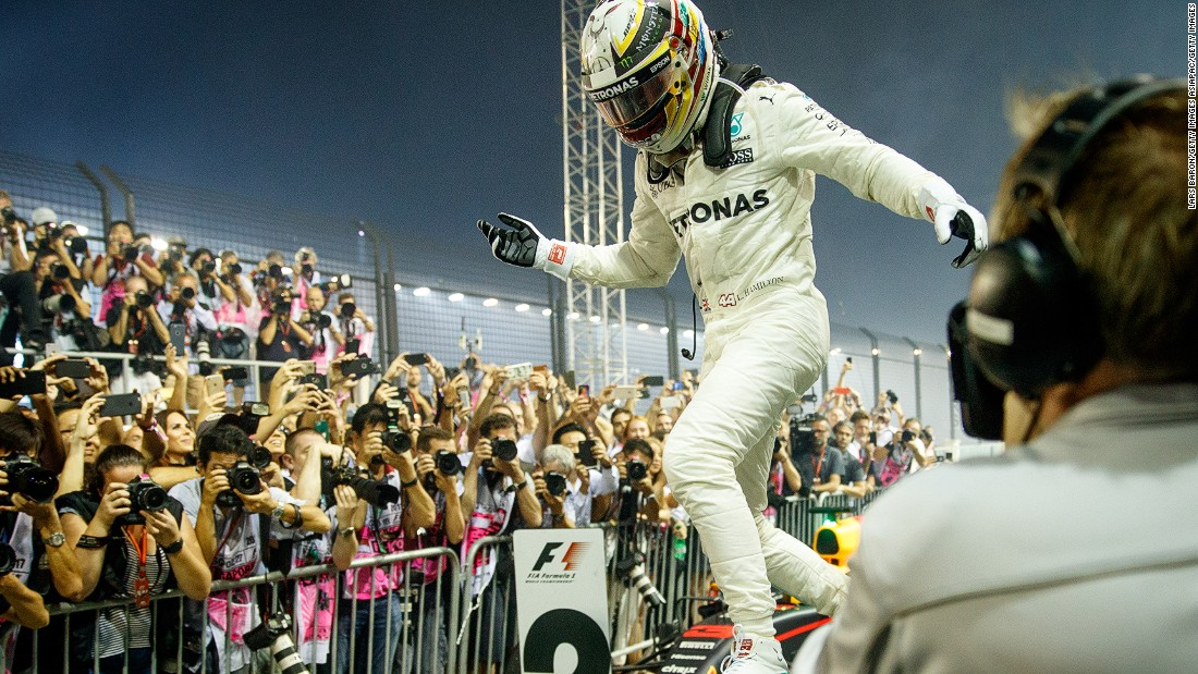 Walking on air: Hamilton leaps off his car following another hugely impressive drive at the Marina Bay Street Circuit. The Briton now leads the drivers' championship by 28 points from Sebastian Vettel.