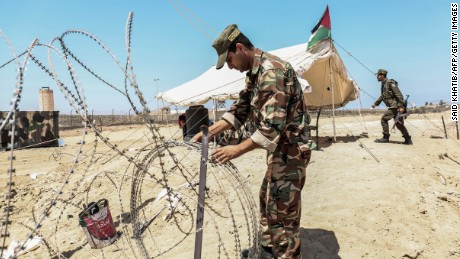 A member of the Palestinian security forces loyal to Hamas installs barbed wire along the border with Egypt near the southern Gaza strip town of Rafah on August 23, 2017.