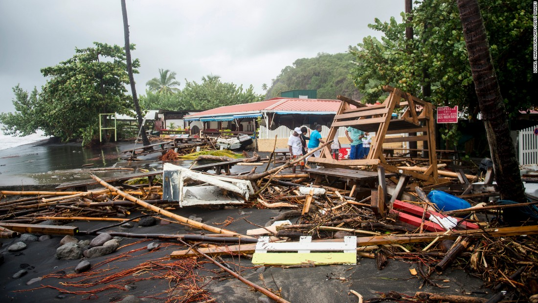 People stand near debris at a restaurant in Le Carbet, Martinique, on September 19.