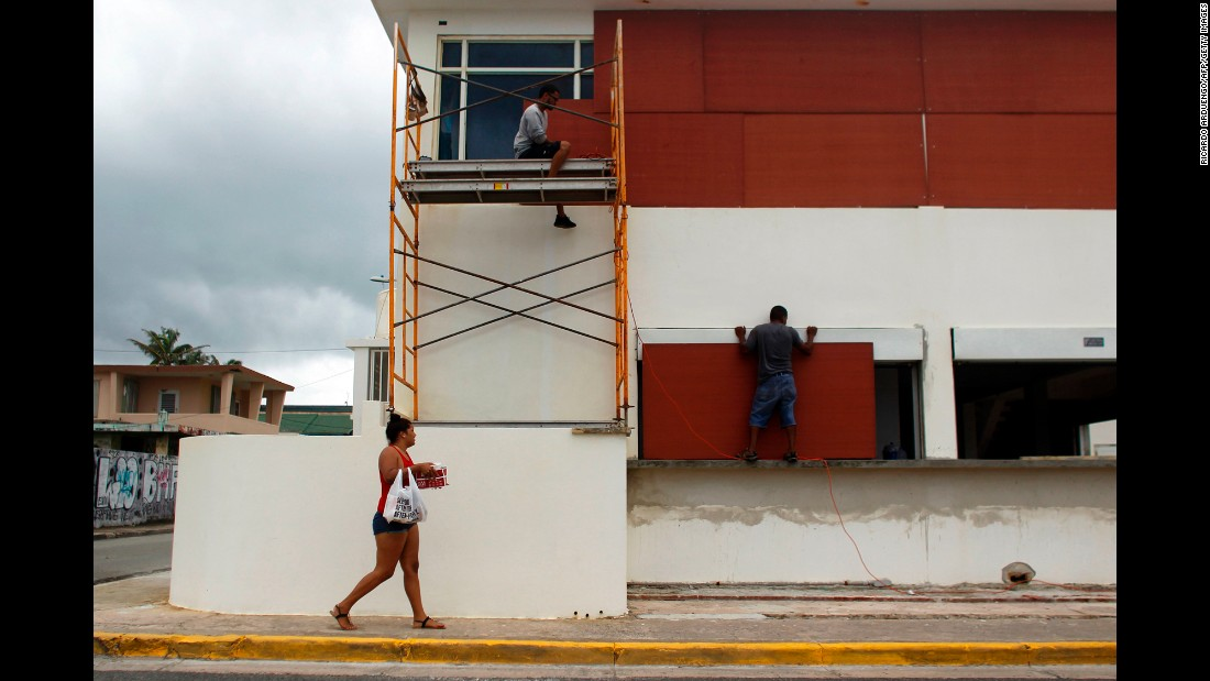 People in Luquillo, Puerto Rico, board up windows of a business on September 19.