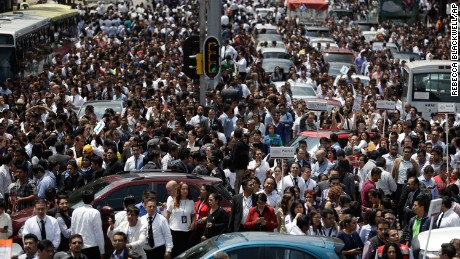 People evacuated from office buildings gather in Reforma Avenue after an earthquake in Mexico City on September 19. A powerful earthquake jolted central Mexico on Tuesday, causing buildings to sway sickeningly in the capital on the anniversary of a 1985 quake that did major damage.