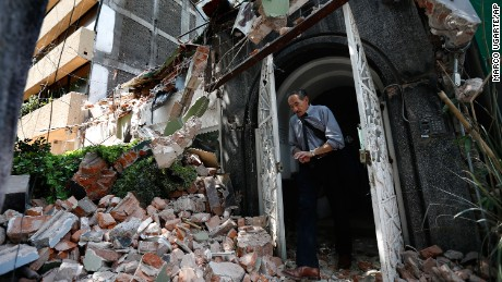 A man walks out of the door frame of a building that collapsed after an earthquake, in the Condesa neighborhood of Mexico City on September 19.