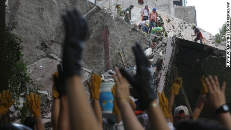 First responders raise their hands asking for silence as they work on removing the rubble of a collapsed building looking for survivors.
