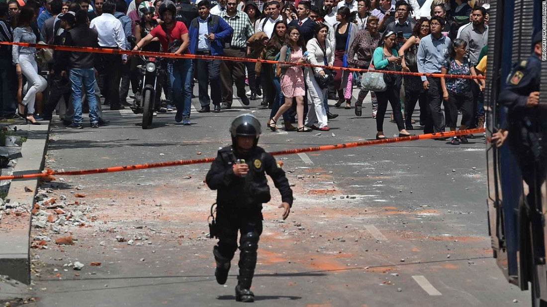 A police officer runs toward the site where a building collapsed in Mexico City on September 19.