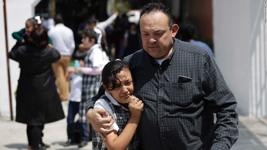 A man comforts a student outside a school in Mexico City on September 19.
