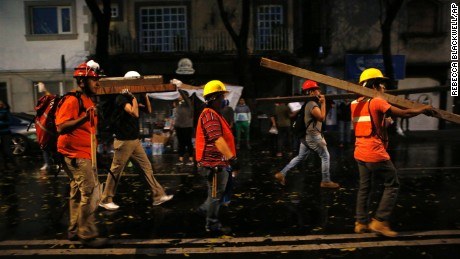 A group of men calling themselves the Insurgentes Brigade arrive carrying beams of wood to offer their services at a site of earthquake damage in the Roma neighborhood in Mexico City, Wednesday, Sept. 20, 2017. City residents are roaming the streets looking for ways to help in the rescue and recovery effort, and thousands have participated in removing debris, organizing donations, directing traffic, and distributing food and water. (AP Photo/Rebecca Blackwell)