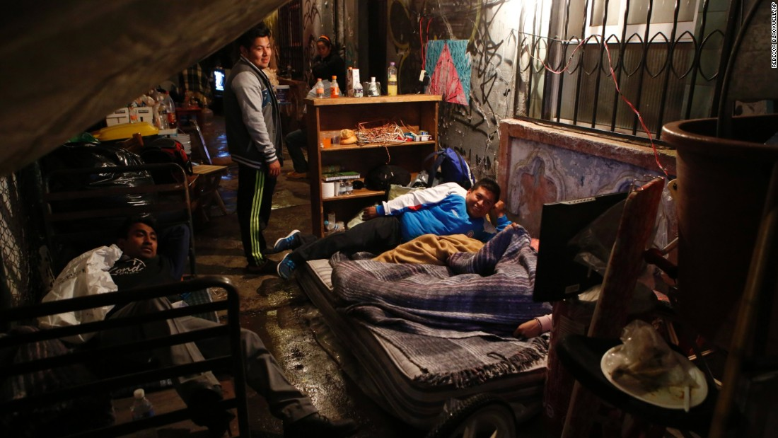 Families prepare to sleep under tarps outside their quake-damaged building in Mexico City on September 20.