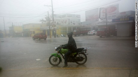 TOPSHOT - A man rides a motorcyle along a flooded street in Punta Cana, in the Dominican Republic, as Hurricane Maria approaches on September 20, 2017.  The government of the Dominican Republic told people to stay home from their public and private sector jobs on Thursday, when the hurricane is expected to hit the island.  / AFP PHOTO / Erika SANTELICES        (Photo credit should read ERIKA SANTELICES/AFP/Getty Images)