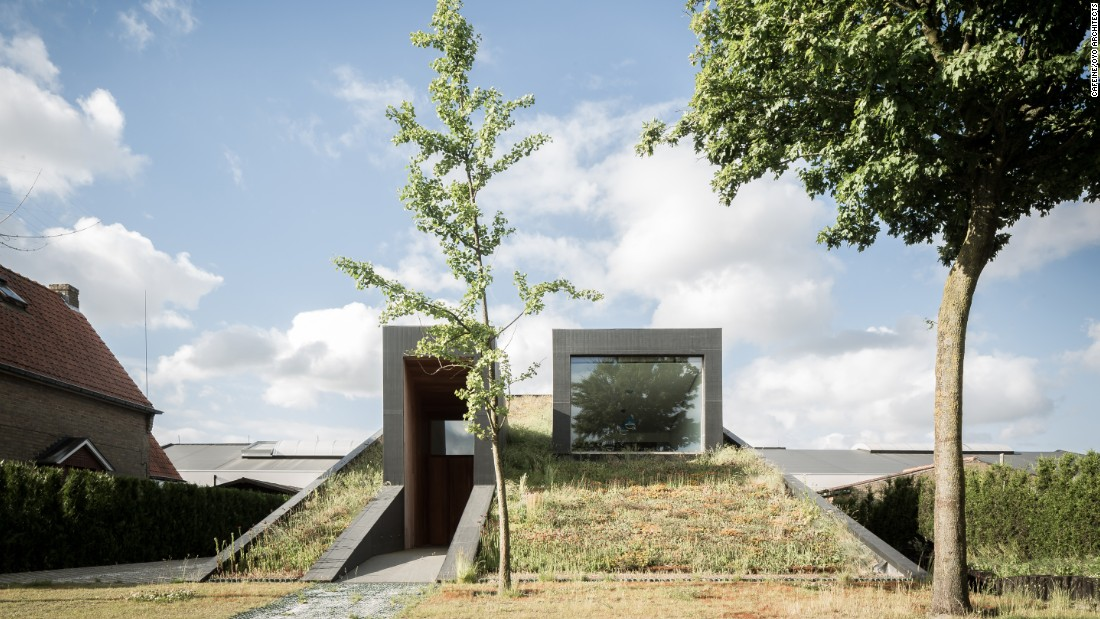 This semi-underground house in Belgium by OYO Architect was designed with a Scandinavian-like ambience, featuring a green roof and bedrooms underground.