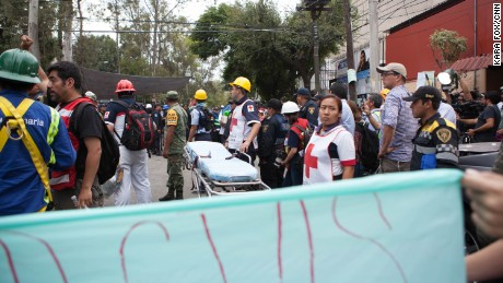 Medics from the Mexican Red Cross stand by with a stretcher.