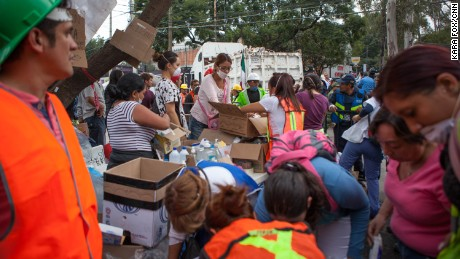 Medics and volunteers sift through donated medical supplies near the school.
