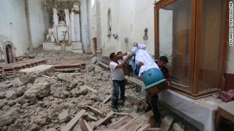 Workers rescue a religious statue from the heavily damaged former convent of San Juan Bautista, in Tlayacapan, Morelos state, Mexico, Wednesday, Sept. 20, 2017. People by the millions rushed from homes and offices across central Mexico, after a 7.1 earthquake, sometimes watching as buildings they had just fled fell behind them with an eruption of dust and debris. (AP Photo/Eduardo Verdugo)