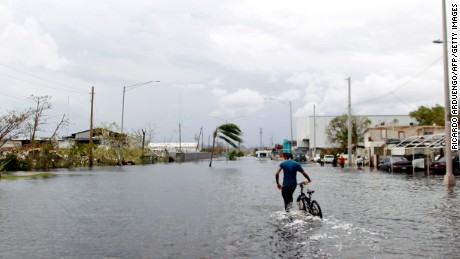 A man wades on the water while pushing his bicycle through a flooded street in the aftermath of Hurricane Maria in Catano, Puerto Rico, Friday, September 22, 2017. Puerto Rico battled dangerous floods Friday after Hurricane Maria ravaged the island, as rescuers raced against time to reach residents trapped in their homes and the death toll climbed to 33. Puerto Rico Governor Ricardo Rossello called Maria the most devastating storm in a century after it destroyed the US territory's electricity and telecommunications infrastructure.