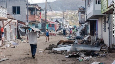 Residents of Roseau, capital of Dominica, walk down a street covered in debris on September 22, four days after Hurricane Maria battered the Caribbean.
