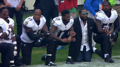 Terrell Suggs, No. 55, and Baltimore Ravens legend Ray Lewis, wearing a sport coat, kneel before Sunday's game.