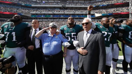 Philadelphia Eagles owner Jeff Lurie joins his players for the national anthem.
