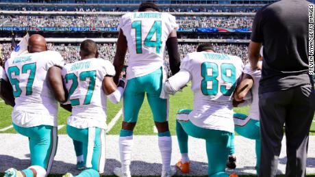 Wide receiver Jarvis Landry stands among his kneeling Dolphins teammates Sunday.