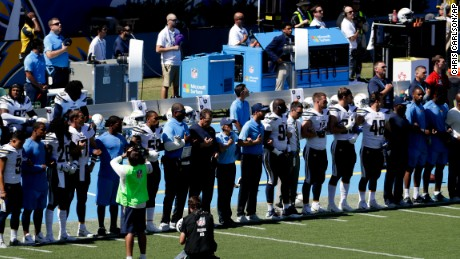 Members off the Los Angeles Chargers lock arms in protest before a football game against the Kansas City Chiefs.