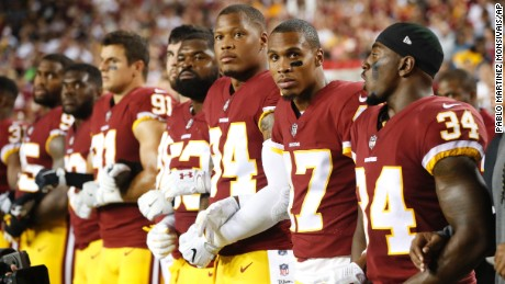 Member of the Washington Redskins stand arm in arm during the playing of the National Anthem on September 24.