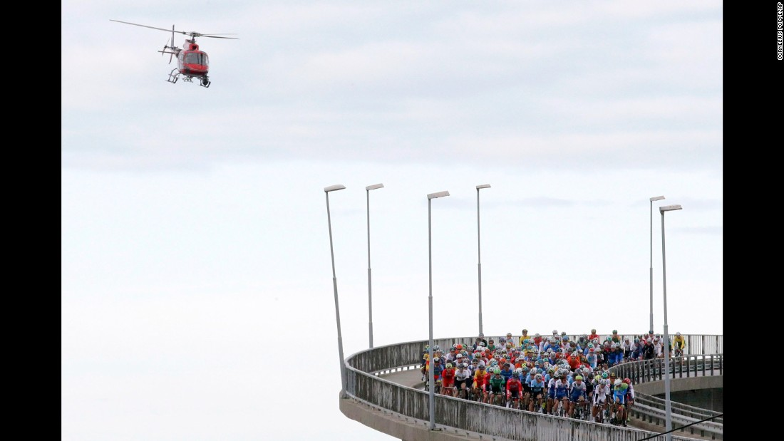 A helicopter flies over cyclists crossing a bridge in Bergen, Norway, during the Road World Championships on Sunday, September 24.