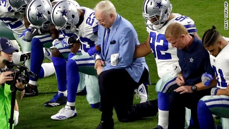 Owner Jerry Jones, center, takes a knee Monday with his team prior to the National Anthem.